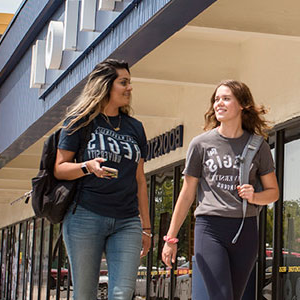 students walk by bookstore at regis square