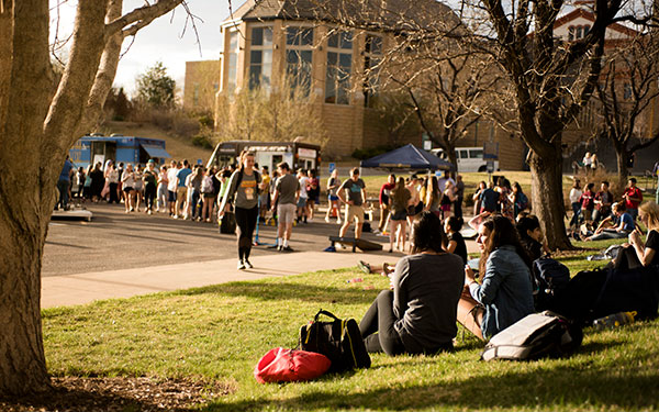 students sit outside during student event