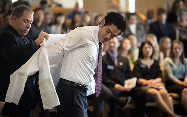 student receiving white coat at graduation