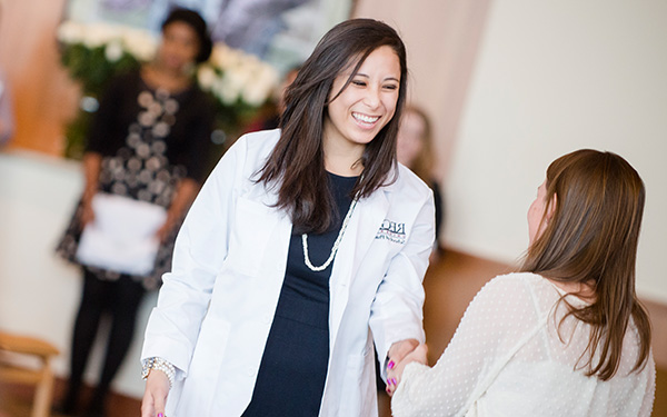 woman in white coat shaking hands