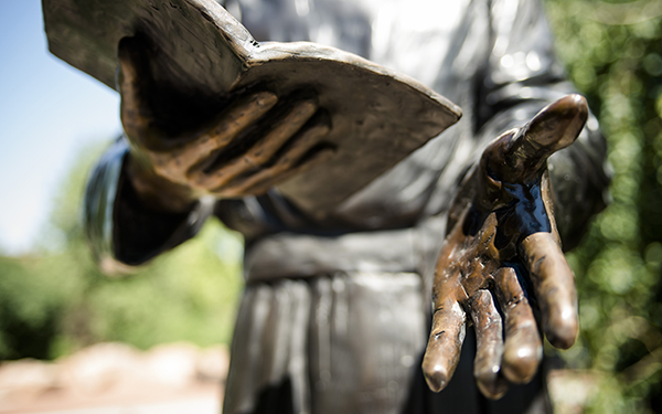 sculpture hands holding bible